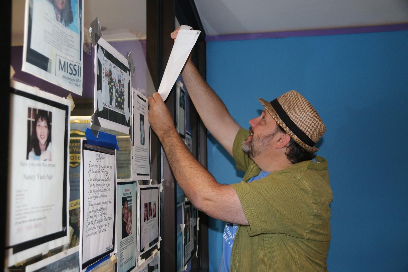 Dave Gordon installing Missing Poster Wall