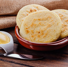 Plate with arepas and butter aside on a