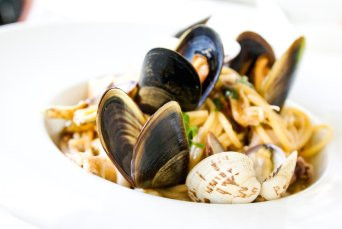 Image of cooked mussels and fettucine in a bowl.