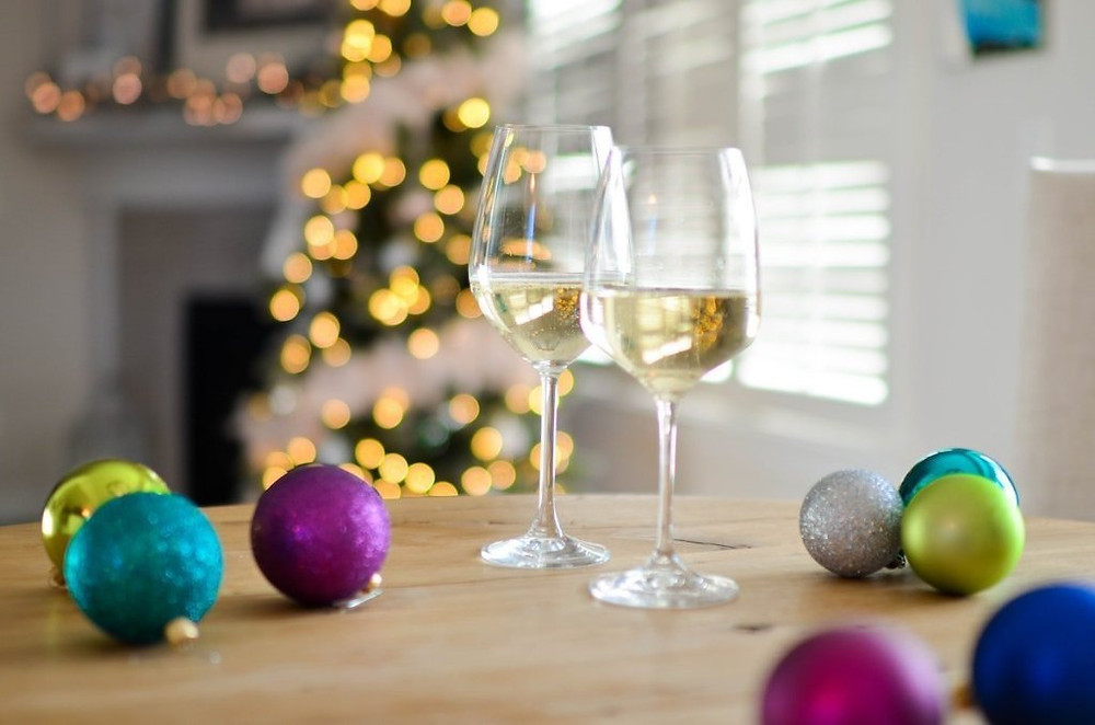 White wine glasses on table with bright ornaments and a Christmas tree in the background.