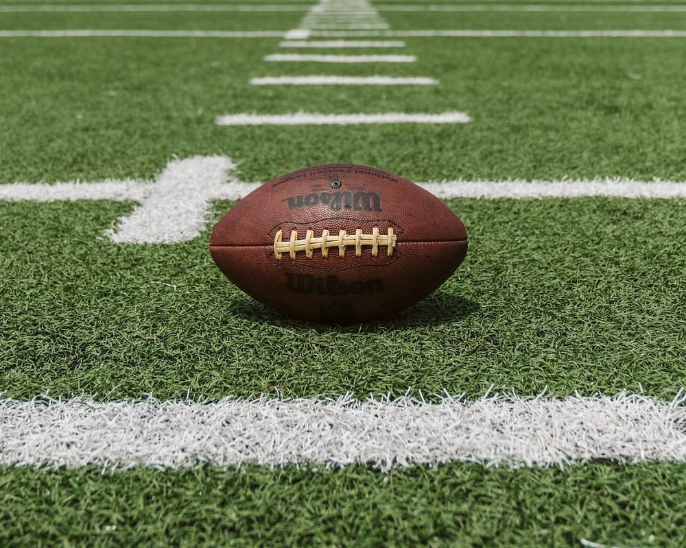 Upclose image of football on football field.