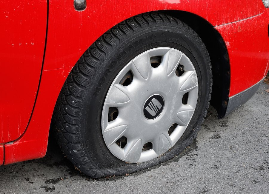 Red car with flat tire.