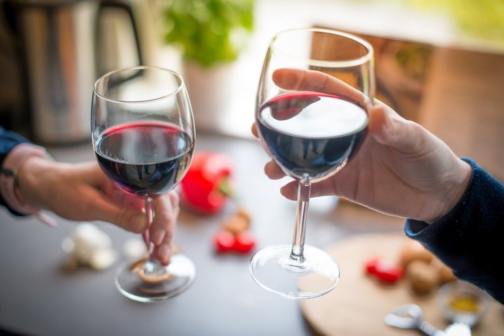 Close up photo of two people toasting with red wine.