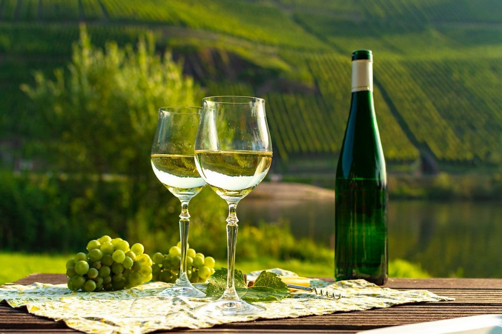 Image of two glasses of Riesling with Riesling bottle and steep sloping vineyards in the Mosel Valley in Germany.
