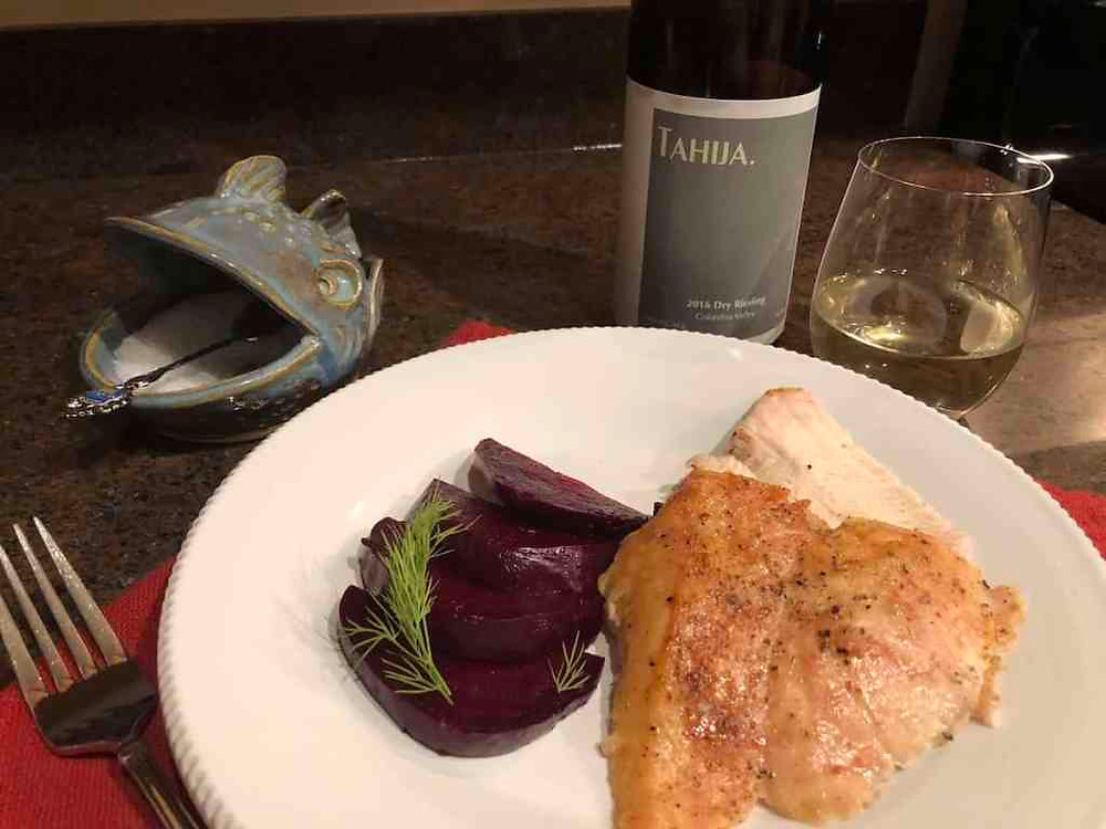 Turkey breast and red beets on a white plate with bottle of Riesling and glass with Riesling.