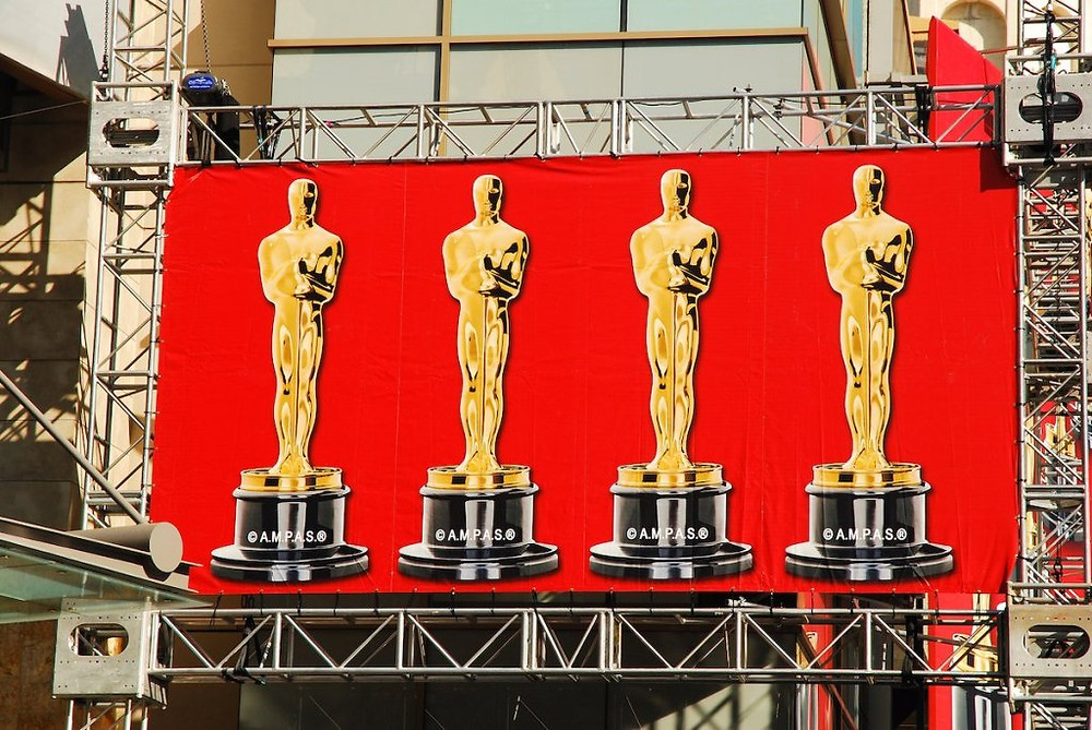 Picture of banner red banner displaying 4 Oscars outside the theater where the Oscars are being held.