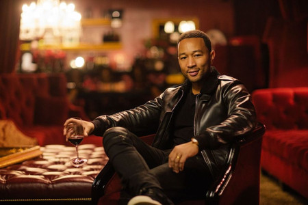 John Legend with glass of wine.