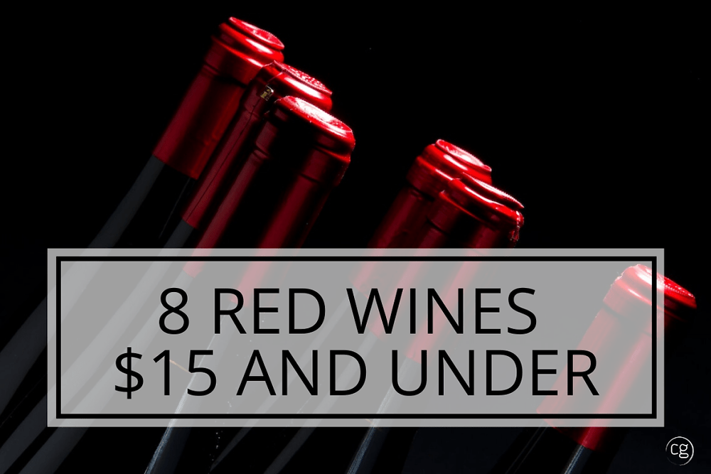 Close up image of wine bottles with Red Foil with text overlay: 8 Red Wines $15 and Under.