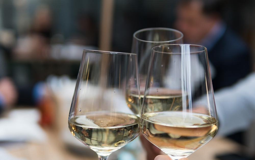 Three white wine glasses toasting.