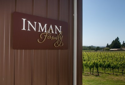 Image of the Inman Family sign and the vineyards in the background.
