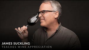James Suckling sniffing a glass of red wine.