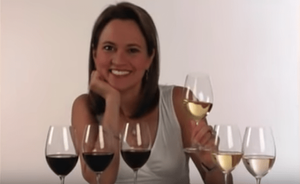 Andrea Robinson, Master Sommelier, with glasses of red and white wine lined up in front of her.