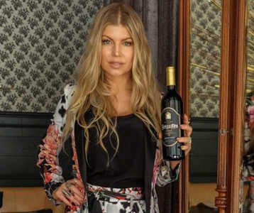 Fergie with bottle of her wine.