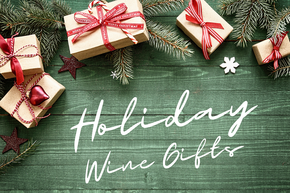 Festive packages and pine branches along with wording: Holiday Wine Gifts.