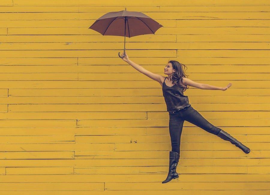 Woman flying away with umbrella.