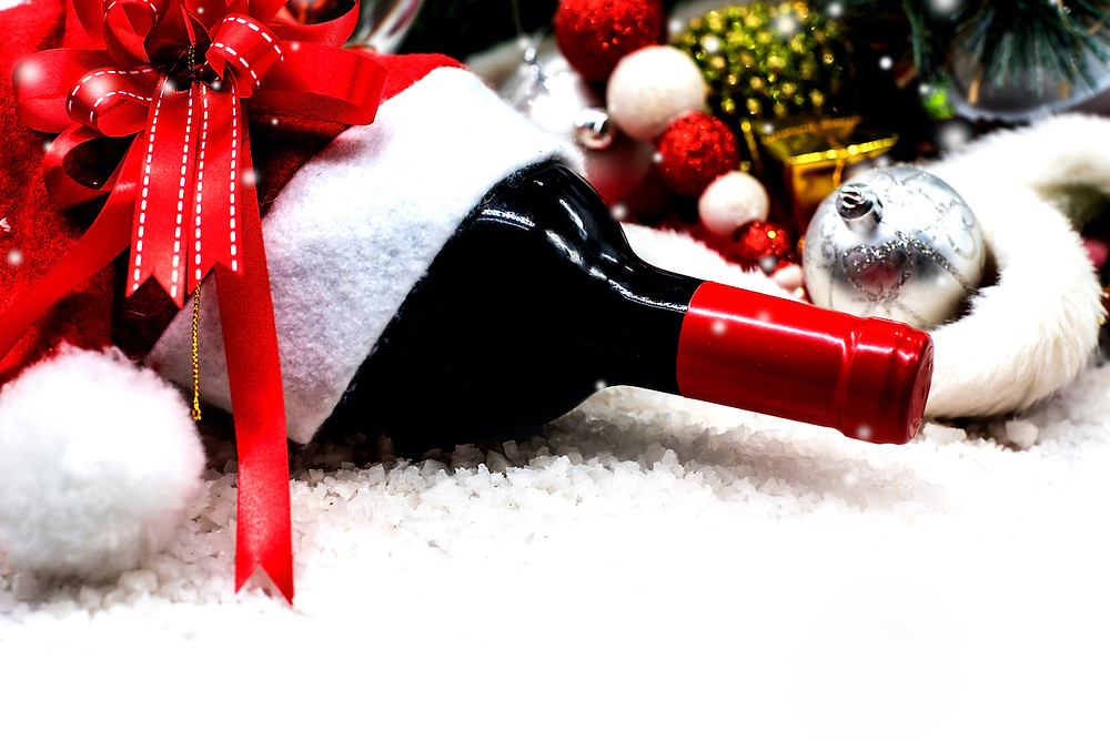 Wine bottle on it's side surrounded by festive holiday decorations.