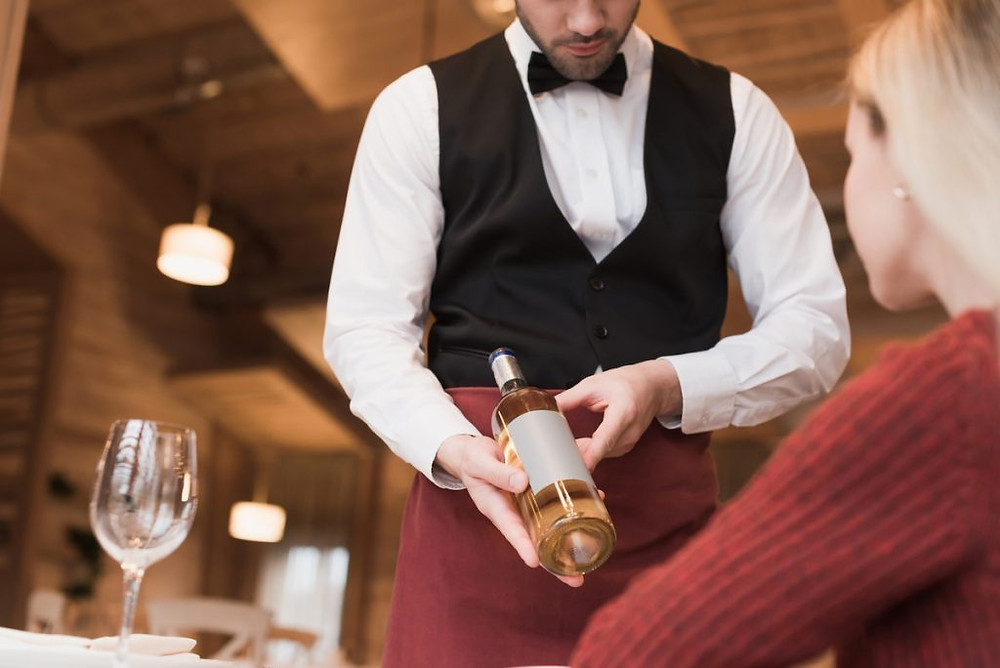 Sommelier presenting wine showing restaurant wine etiquette.