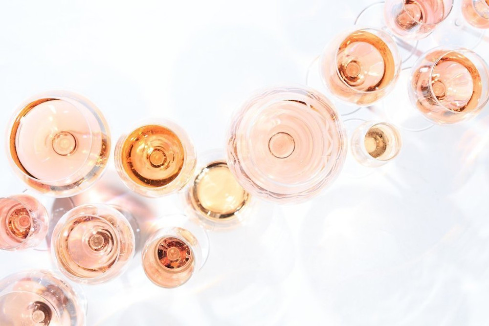 Overhead view of many glasses of rose wine at wine tasting.