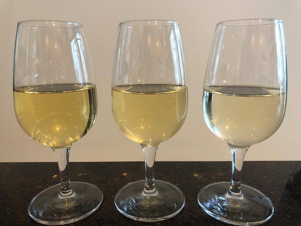 Three wine glasses with white wine.