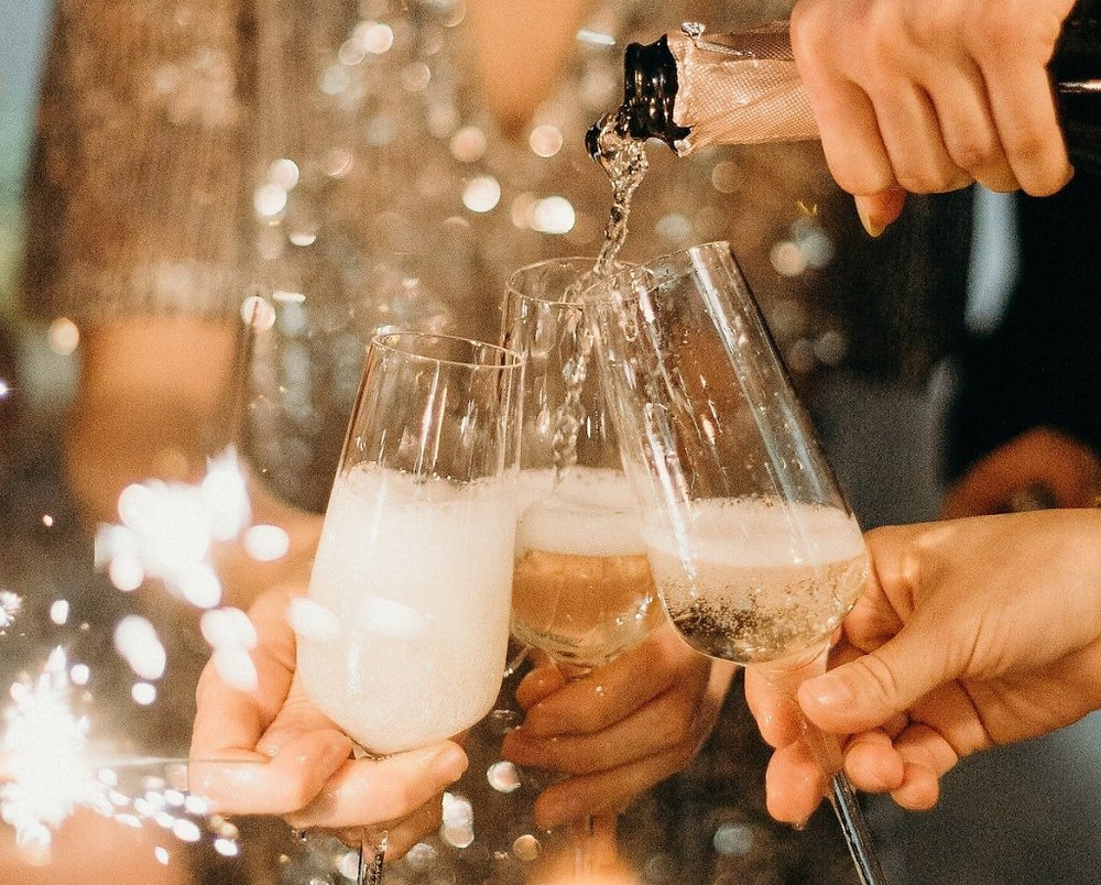Champagne being poured into glasses with sparklers for a celebration.