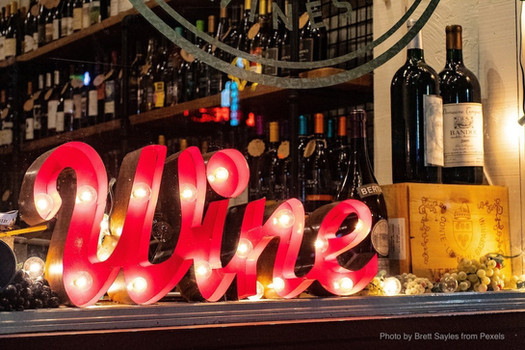 Wine sign with lights sitting on bar.