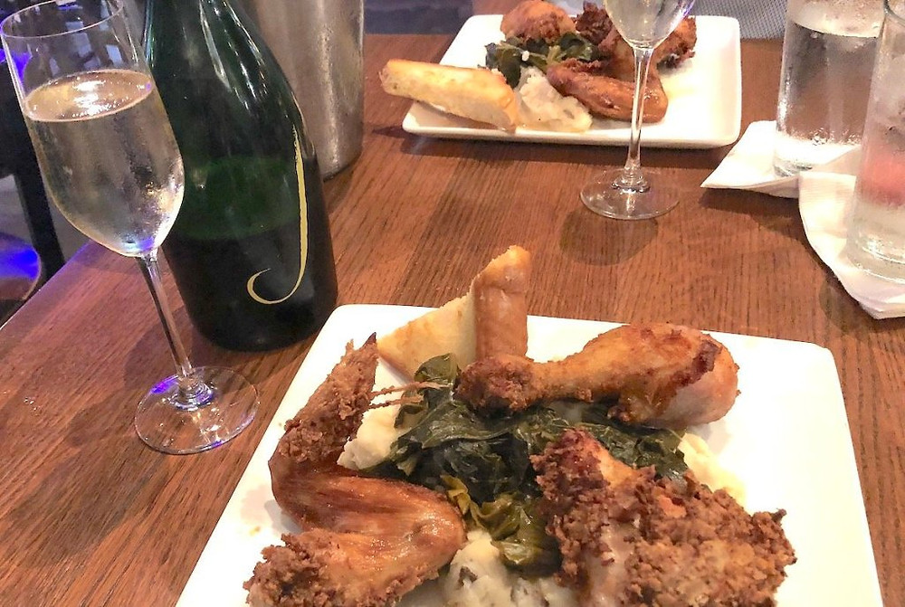 Plate of fried chicken on top of mashed potatoes and collard greens with a bottle and glass of Champagne.
