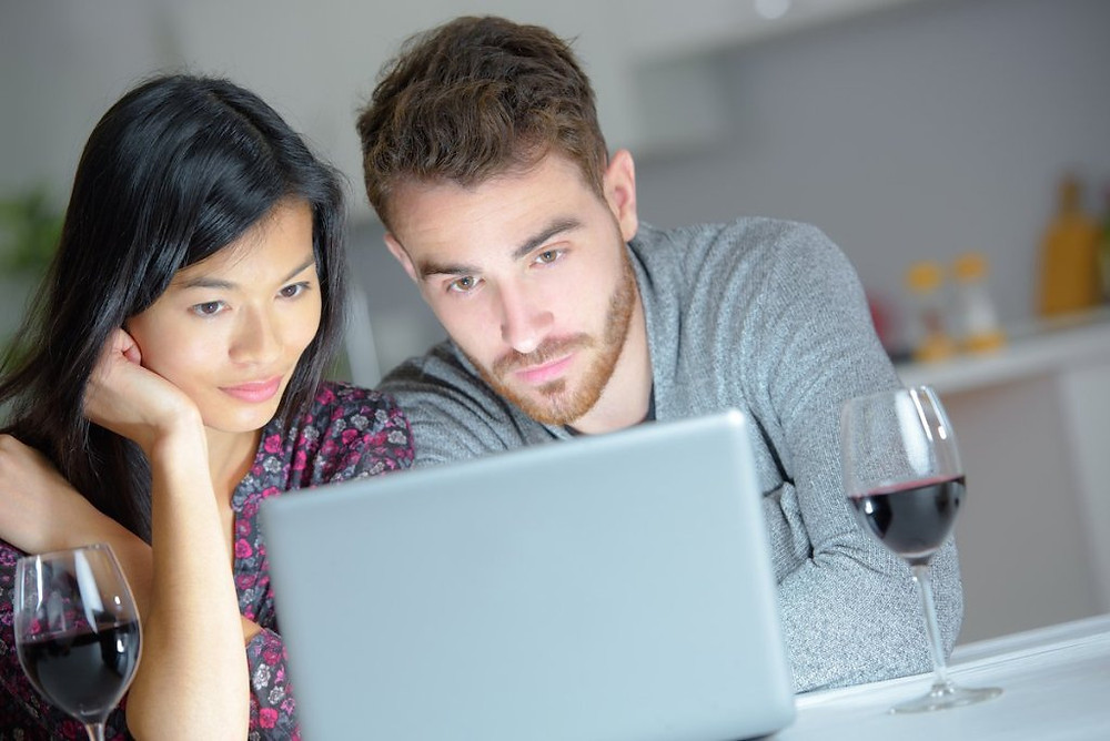 Couple watching laptop with glasses of red wine next to them.
