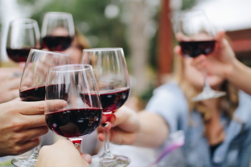 Close up image of group toasting with red wine.