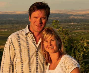 Picture of Drew and Maura Bledsoe with their vineyard in the background.
