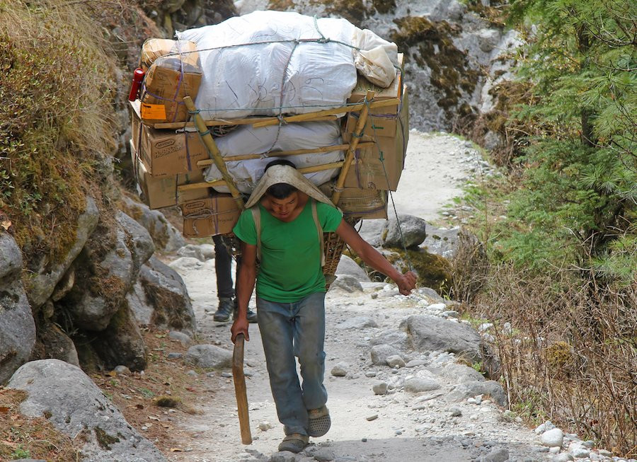 Man carrying a heavy load on his back.