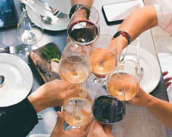Friends toasting with wine glasses at the table | commongrape.com
