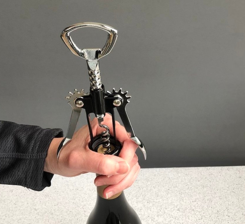 Wing corkscrew showing placement on top of wine bottle.