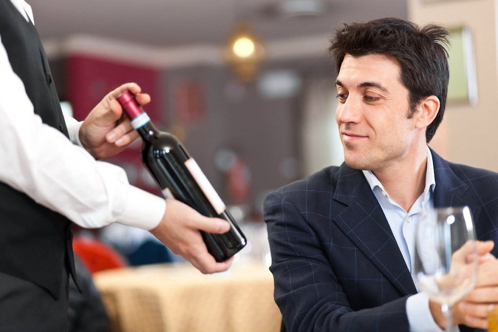 Sommelier presenting wine bottle to restaurant guest.