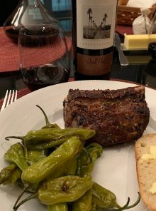 Plate of short ribs with bottle and glass of Syrah.