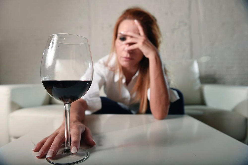 Woman holding her head with a glass of red wine in front of her.