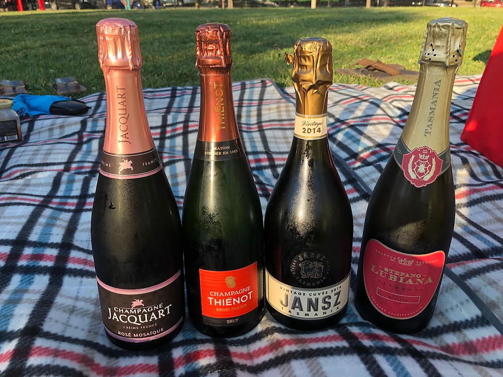 Four Bottles of bubbly on a picnic blanket.