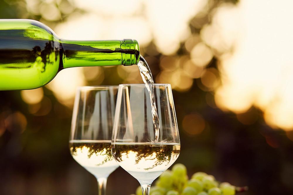 Pouring Sauvignon Blanc into two glasses of wine.