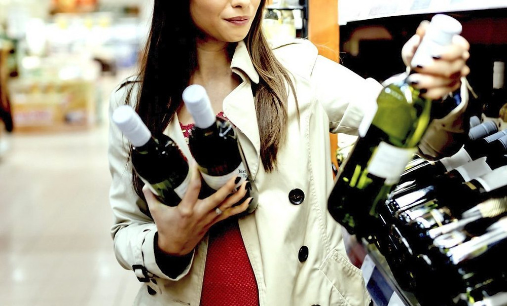 Woman deciding what wine to buy in a supermarket.