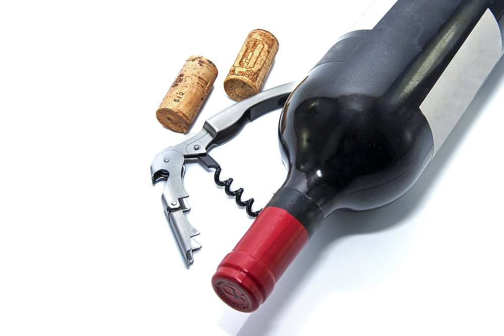 Red wine bottle on its side with a corkscrew and 2 corks next to it.