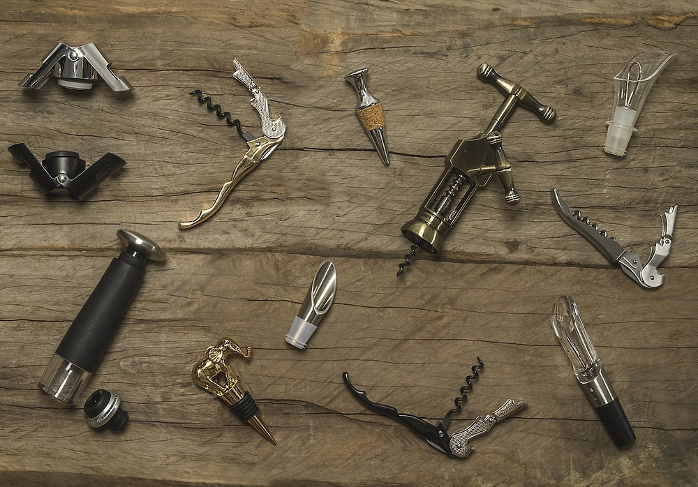 A variety of Wine Tools on a wood table.