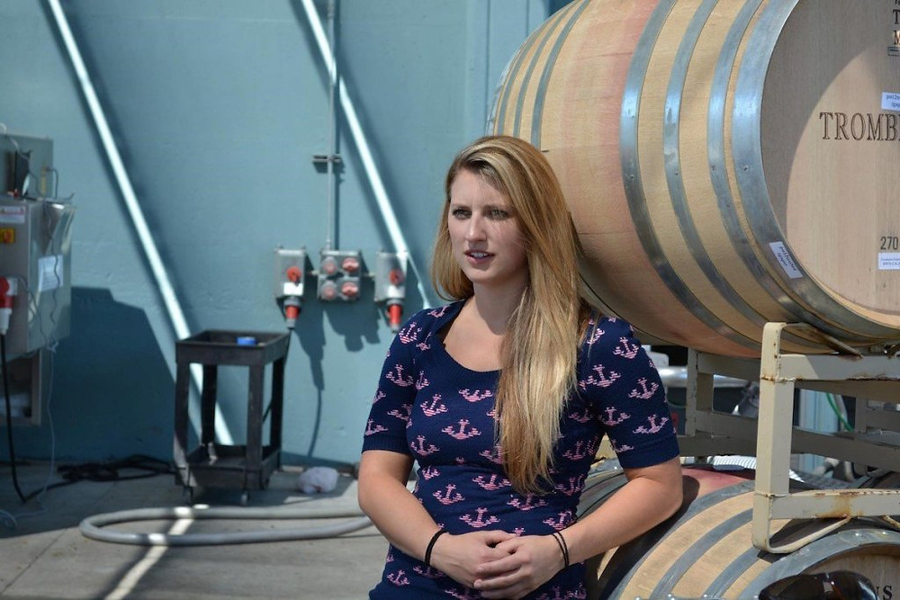 Erica Stancliff leaning against oak barrels. She is one of the female winemakers making history.