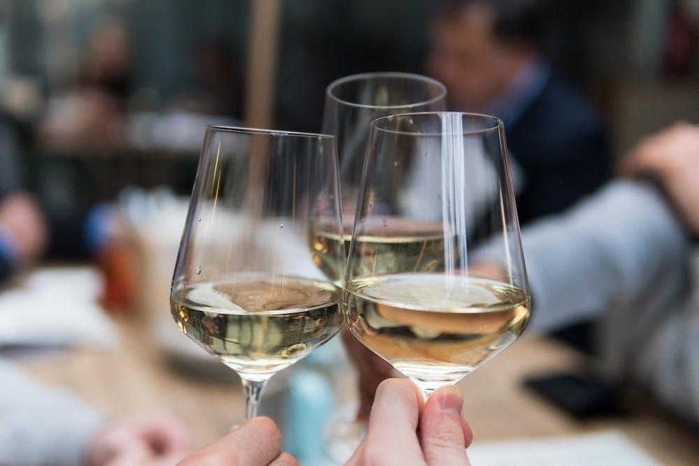 Upclose image of 3 white wine glasses toasting at a restaurant.