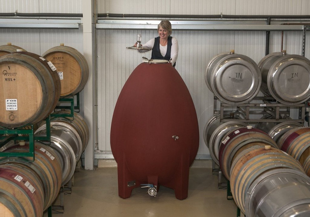 Image of Female Winemaker, Kathleen Inman, working with wine in a concrete egg.