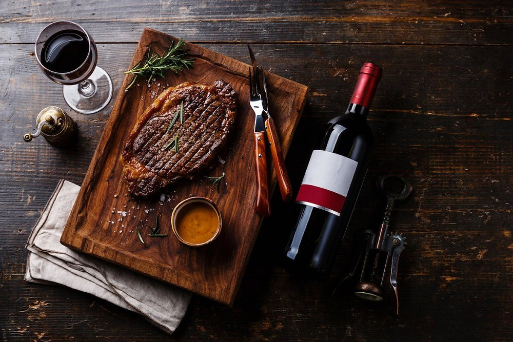 Grilled sliced Steak Rib eye with Pepper sauce and bottle of Red wine on wooden background.