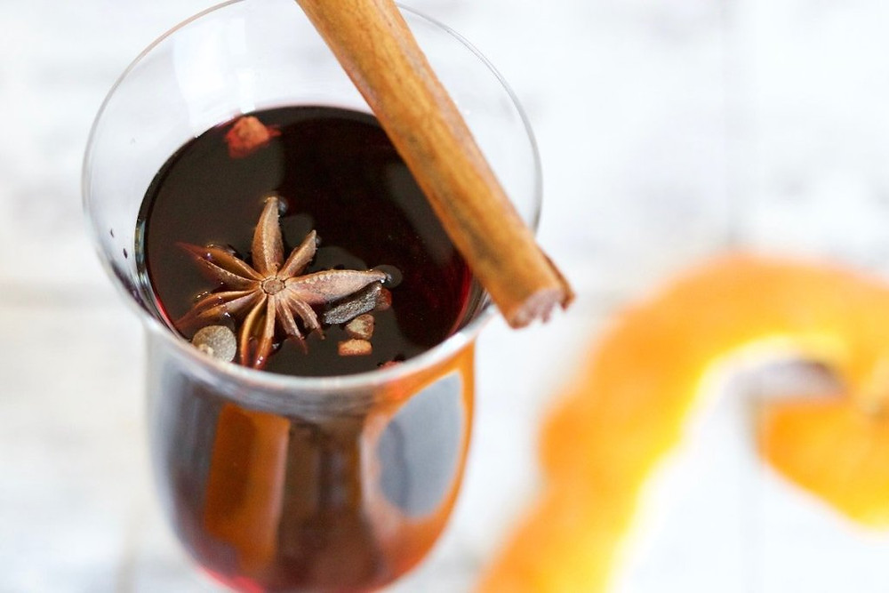 Glass mug of mulled wine with garnish of star anise and cinnamon stick.