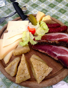 A typical start to any high mountain meal: Mountain cheese, speck (cold smoked meat), Tirolean Grey cheese, Kaminwerst, and assorted hard breads and butter.