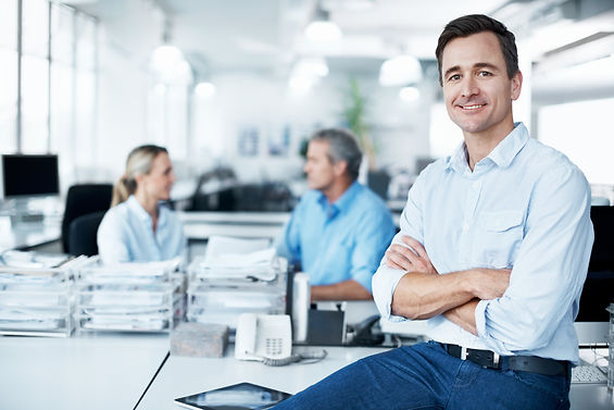 Happy business owner sitting on desk_XL_