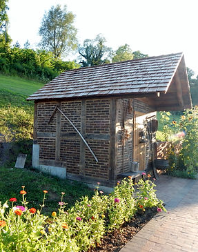 Re-built historic timber frame with brick fill and cedar shake roof used as garden shed