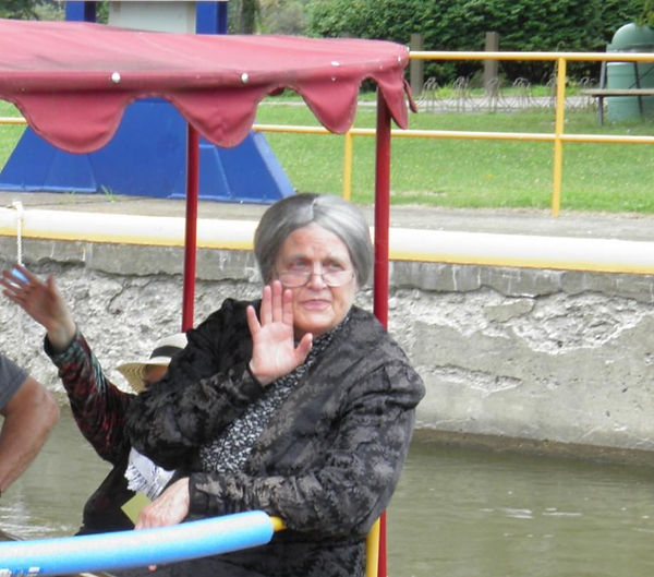 An Actor Dressed as Susan B Anthony waves from the back of a boat on the Erie Canal