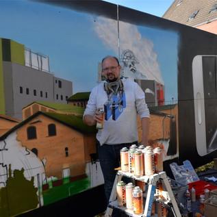 Graffiti-Künstler Sebastian Rolf bringt Bergbaugeschichte auf Bauzaun